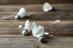 Shuttlecock with parts of its feathers scattered on wooden. Royalty Free Stock Photography