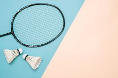 Shuttlecock and racket for playing badminton on a pástel color royalty free stock photography