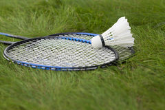 Shuttlecock with rackets on the green grass. Stock Photos
