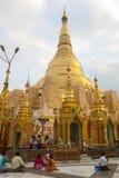 Shwedagon Paya. With people praying at its base Royalty Free Stock Photos