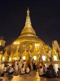 Shwedagon Paya by Night. With people praying at its base Stock Images