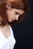 Shy... Sensual girl in white, with pearls , posing on black background stock photography