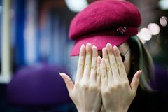 Shy. A girl covers her head with her hands royalty free stock photography