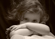 Shy. Young girl hides behind her arms, being shy Royalty Free Stock Image