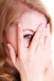 Shy afraid woman peeking through fingers isolated. Royalty Free Stock Photos