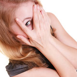 Shy afraid woman peeking through fingers isolated. Stock Images