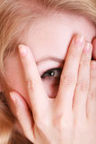 Shy afraid woman peeking through her fingers Stock Photo