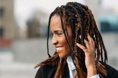Shy African American female. Happy model. Smile. Young black woman smiling in selective focus outdoors, fashion hairstyle, happiness concept royalty free stock photos
