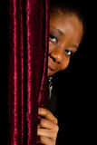 Shy african woman. Young African Ghanese woman hiding shy behind a curtain Stock Photos