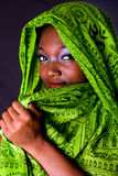 Shy African woman with scarf. The face of an shy innocent beautiful young African-American woman covering her mouth with green headwrap and purple-green makeup Royalty Free Stock Photo