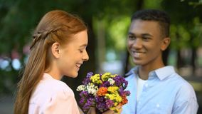 Shy Afro-American boy presenting bouquet of flowers to smiling girl in park. Stock footage stock video footage
