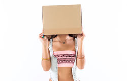 Shy anonymous girl standing with her face hidden under a cardboard box, wearing summer teen outfit and bright Royalty Free Stock Images