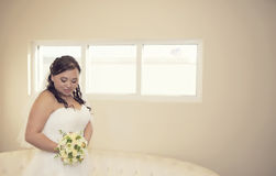 Shy asian bride. A beautiful bride standing looking down at her bouquet royalty free stock photos