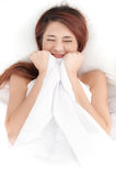 shy asian woman under a duvet Stock Photo