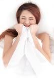 Shy asian woman under a duvet Stock Photo