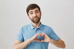 Shy attractive caucasian man showing heart gesture over chest, smiling with closed lips and looking with tender. Expression at camera, as if being asked by stock images