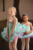 Shy Ballet Students. Shy little girls in ballet dresses at a dance studio Royalty Free Stock Photography
