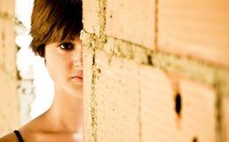 Shy beauty. Shy beautiful woman staring at camera behind brickwall Royalty Free Stock Photography