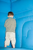 Shy boy. A young boy hides in the corner of a bouncy castle stock photos