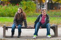 Shy boy and the girl sitting in the park. And lightly touching each other finger tips Royalty Free Stock Photography