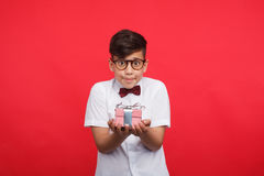 Shy boy outstretching hands with giftbox. Little modest boy in glasses holding small giftbox on hands and looking at camera on red royalty free stock photo