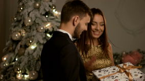 Shy boyfriend gifting a present for his beautiful smiling girlfriend near Christmas tree. Shy boyfriend gifting a present for his beautiful smiling girlfriend stock footage