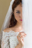 Shy bride behind curtains Stock Image