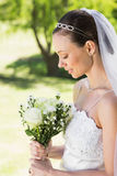 Shy bride holding bouquet in garden Stock Image