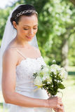 Shy bride holding flower bouquet in garden Royalty Free Stock Photos