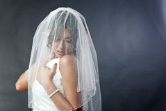 Shy bride with veil. Young shy bride with white wedding dress and veil over her face Royalty Free Stock Images