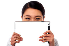 Shy corporate lady hiding her face. Shy smiling asian woman hiding her face with tablet pc Stock Photos