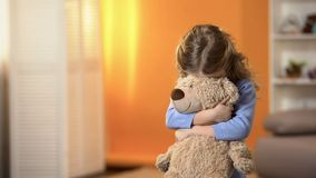 Shy Curly Girl Hiding Face Behind Favorite Teddy Bear, Childhood Psychology Stock Image