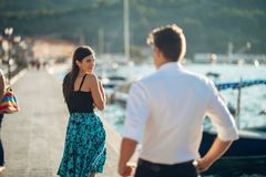 Shy flirty woman smiling to a man.Man giving a compliment to a introvert passing woman.Receiving a compliment on the street.Public royalty free stock image