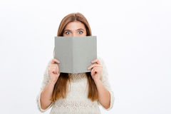Shy generade ungt kvinnligt nederlag bak grå färgboken Royaltyfri Foto
