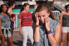 Shy Giggling Girl at Park. Shy giggling teenage girl covering her face at carnival Stock Image