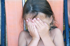Shy girl. A caucasian young girl covering her face with her hands Stock Image