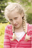 Shy girl. A young pretty shy blonde girl in a park stock photo