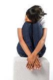 Shy girl. A shy young girl with her knees pulled up to her stomach and her head resting on them on white background royalty free stock photography