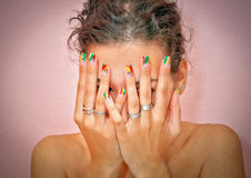 Shy girl. Female hands with crazy colored decorated manicured nails. Jewelry, such as rings are inevitable addition on woman's hands.Young girl is very shy so Royalty Free Stock Images