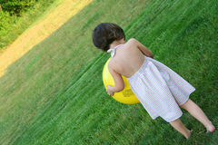 Shy Girl. Playing with a ball in her yard royalty free stock photography