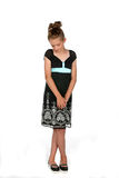 Shy girl in black dress. With legs and hands crossed and looking down royalty free stock photography