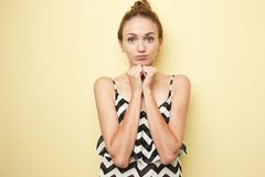 Shy girl dressed in a striped top keeps hands under the chin on the yellow background in the studio royalty free stock photography