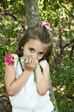 Shy Girl with Flower. Pretty little shy girl holding a pink flower Royalty Free Stock Image
