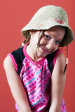 Shy girl with a hat. Girl with a hat and braids making a shy expression Stock Photography