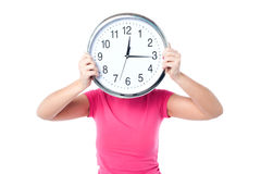 Shy girl hiding her face with wall clock. Young girl hiding her face behind wall clock Royalty Free Stock Images