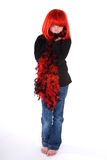 Shy girl in red wig and boa. Stock Images