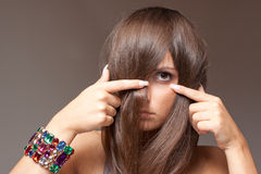Shy Girl spy through the hair. Portrait of beautiful teen with shy look Stock Image