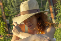 Shy girl in a summer hat enjoying the sun Royalty Free Stock Photos