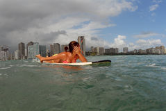 Shy girl surfer. A shy bikini surfer teen girl paddling out stock images