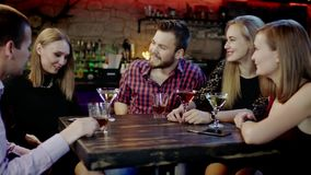 Shy girl is telling something funny in the bar